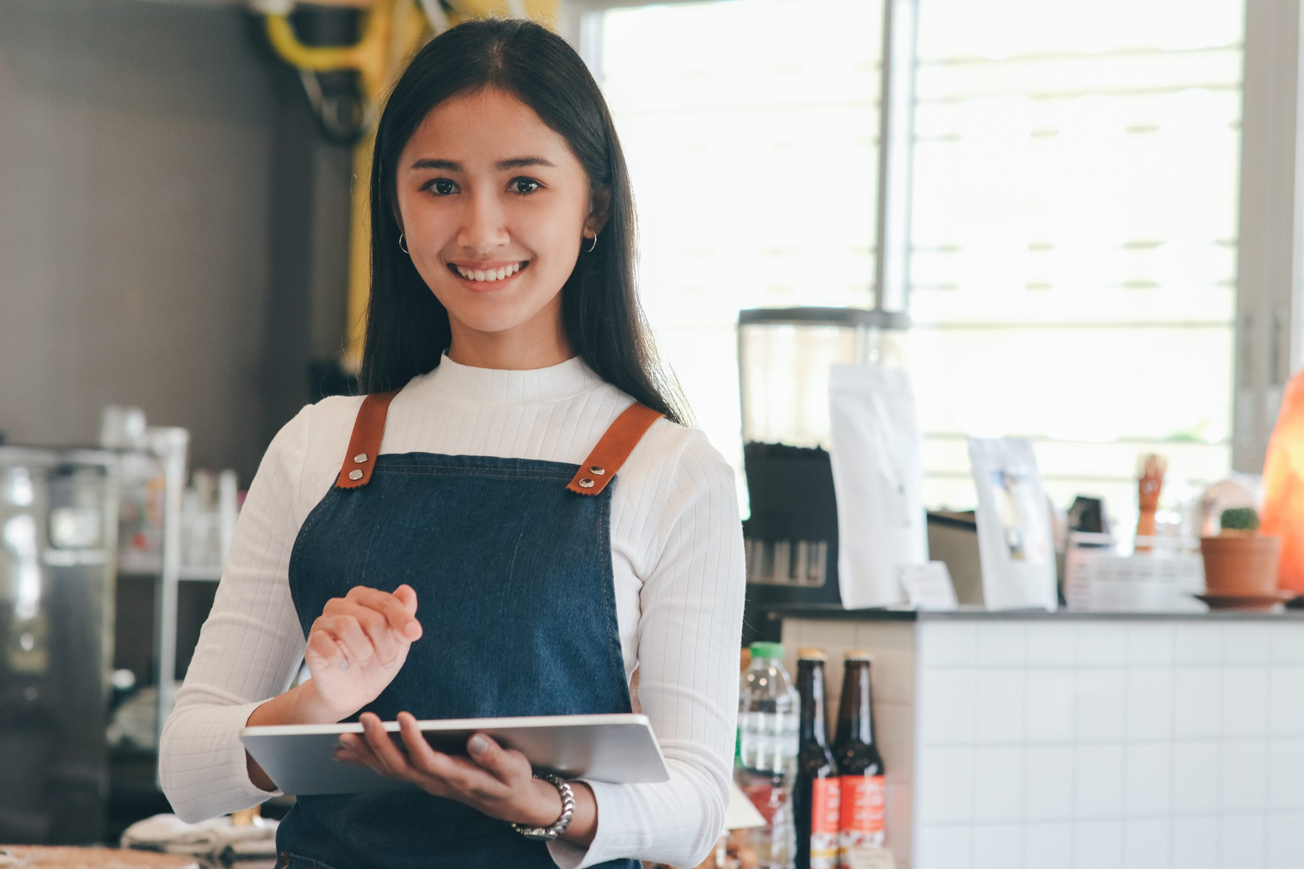 Portrait of woman small business owner using digital tablet and standing in front of counter bar in coffee shop.