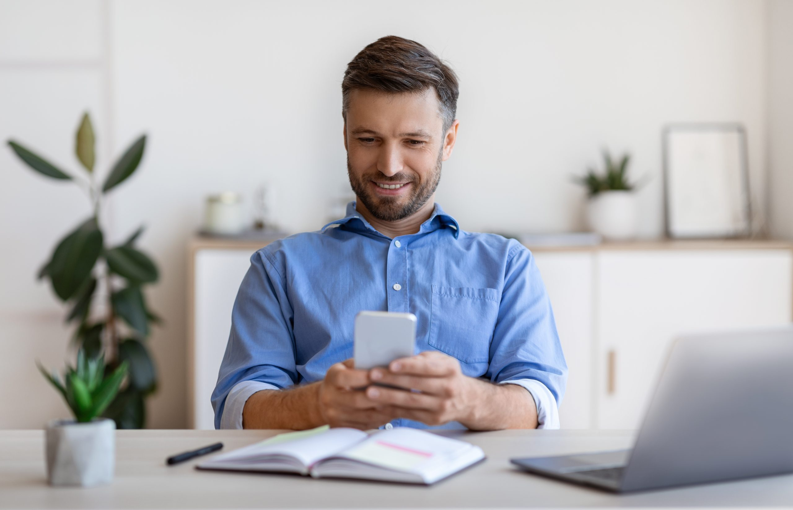 Smiling Business Man Messaging On Smartphone While Relaxing At Workplace In Office, Texting With Friends Or Family, Enjoying Mobile Communication, Having Break In Work, Sitting At Desk With Laptop